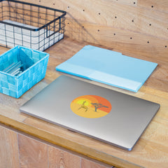 Closed gray laptop computer on a wooden shelf surrounded by office things.  On the top of the laptop there is a round sticker with a bright orange sunset, and in the foreground there is a tree and a yellow origami giraffe.