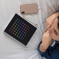 "Girl laying on her bed using headphones and listening to music from her phone.  There is a black spiral bound notebook in front of her that has 49 origami paper cranes printed on the cover in a rainbow order, and has the words ""The Timeless Crane"" across the bottom."