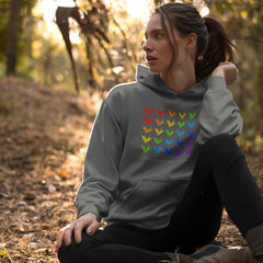 "Young pretty woman sitting in a wooded clearing wearing a dark gray hoodie with 25 origami paper cranes in rainbow order across the front.  At the bottom of the cranes the words ""The Timeless Crane"" are written in a script font."