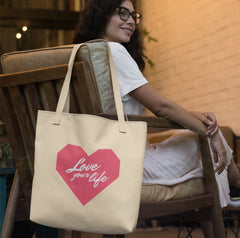 "A pretty young woman wearing glasses is sitting on a padded chair with her tote bag hanging on the side of the chair.  The tote bag is made of canvas and has a large pink origami heart printed on it with the words ""Love your life"" written inside of the heart in white script."