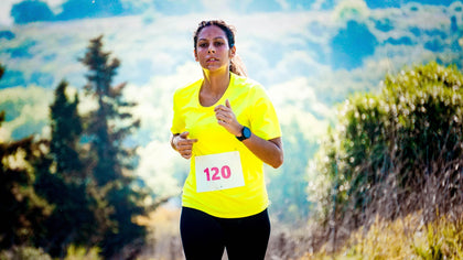 Image of a female jogger in a yellow shirt with a fitness tracker and sports headphones.