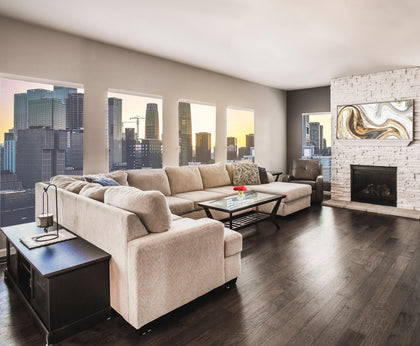 This is a picture of a modern living room with a large tan sectional sofa on a brown hardwood floor with the image of a city skyline outside. Find it at knecthome.myshopify.com