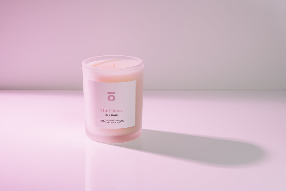 HBFace custom scented candle. Organic and natural cedarwood and amber candle on a white background with pink lighting.