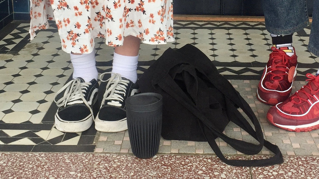Two young women using a Reusable cup and bag for Plastic Free July