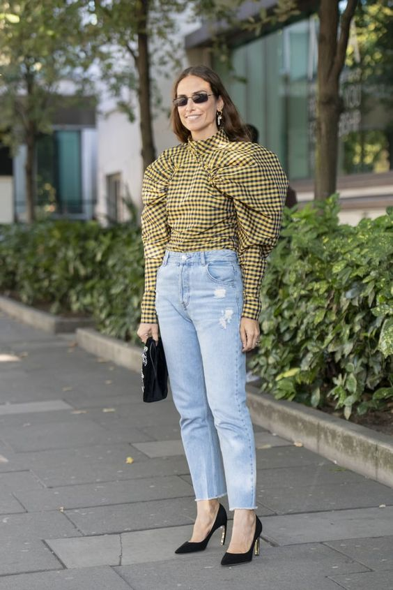 Women standing outside with puff sleeve yellow and black shirt with denim jeans