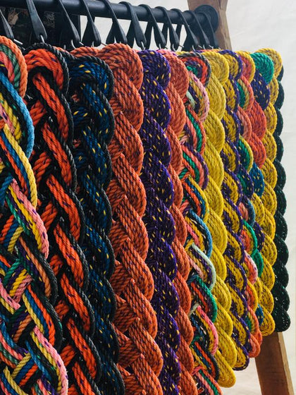 Hanging vibrant colored welcome mats made with upcycled lobster rope