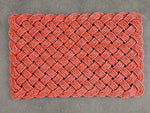 Maine mudroom mat made from orange upcycled lobster rope with blue flecks