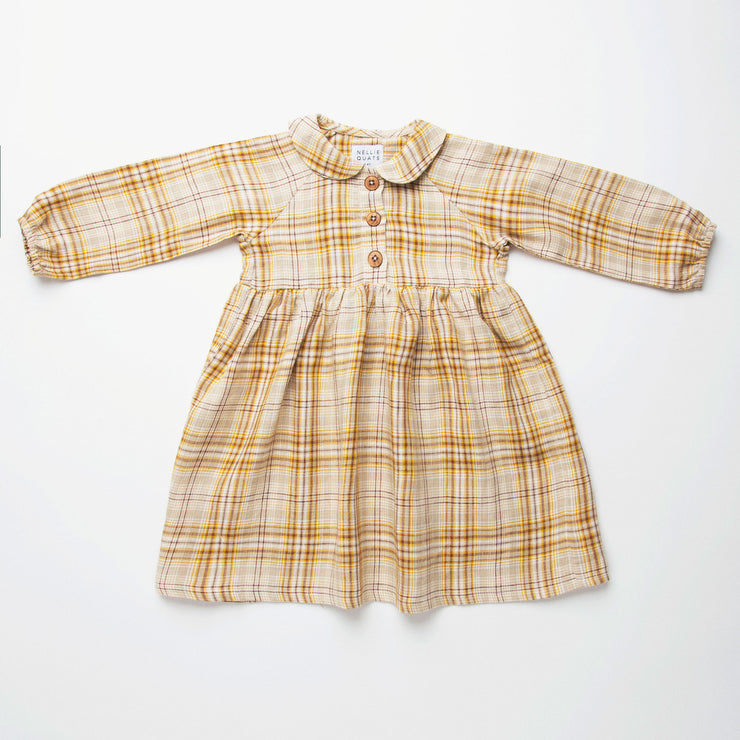 Long sleeve raglan dress with empire line, elasticated cuffs, Peter Pan collar and wooden button up front. Attached gathered skirt sits at a slightly longer length below the knee. Designed to be oversized for a stylish, comfortable fit. Made from a buttermilk plaid linen.
