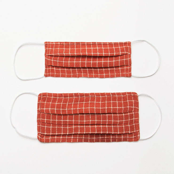 Reusable, triple layer, linen face mask, with soft rounded elastic ear loops, pleated shape and soft wire to shape to the nose. Made from rust check linen outer, a single layer of plain cotton in the middle and milk white linen on the inside to sit against face (this linen will either be plain or the polka dot from the collection - the polka dot is not a noticeable texture and still comfortable on the skin).