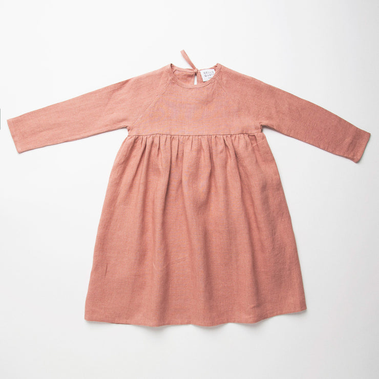 Long sleeve raglan dress with empire line and tie at the back of the neck. Made from medium-weight dusty rose linen. Attached gathered skirt sits at a longer length below the knee. Designed to be oversized for a stylish, comfortable fit.