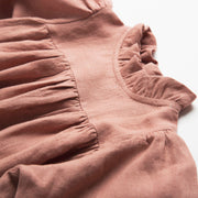 Full, floaty dress, with high empire line, full elasticated sleeves, small neck ruffle and mother of pearl buttons down the back yolk. Attached gathered skirt sits at a longer length below the knee. Designed to be oversized for a stylish, comfortable fit. Made from beautifully soft, dusty rose linen.