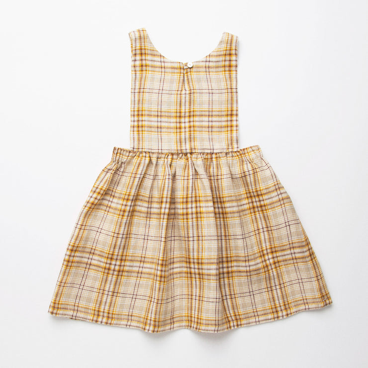 Simple pinafore shaped dress, with tabard style bib and loose fit gathered skirt for a comfortable fit. Top does up through single mother of pearl button on the back of the neck. Made from soft, buttermilk plaid linen. Designed to sit above the knee. Designed for all seasons, perfect for layering in cooler weather or stripping back in the summer.