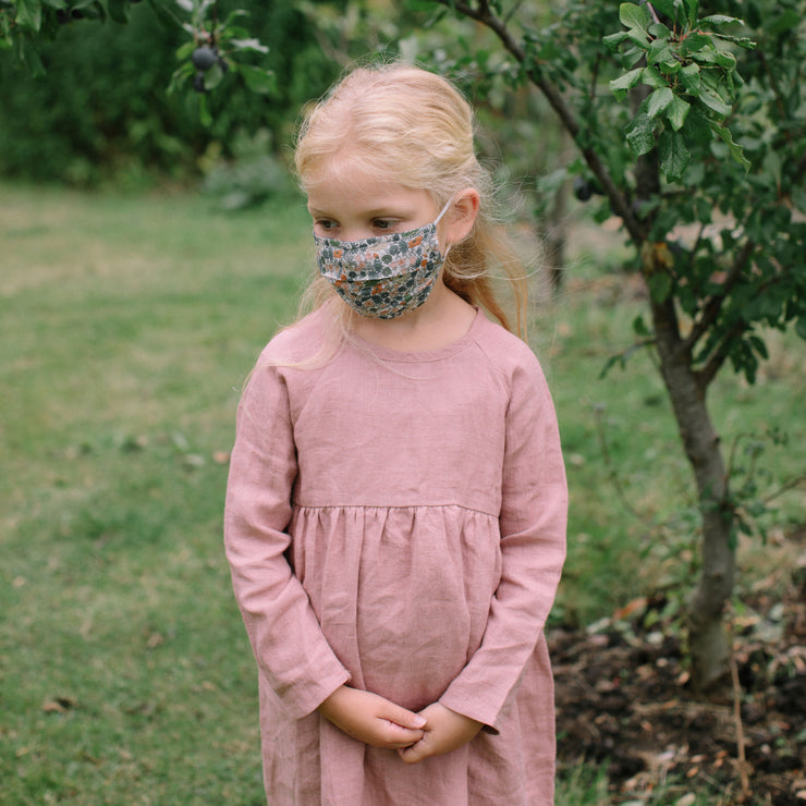 Reusable, triple layer, cotton face mask, with soft rounded elastic ear loops, pleated shape and soft wire to shape to the nose. Made from Poppy & Daisy Liberty print outer, with two additional layers of plain cotton.  Please note these are not medical grade face masks and should be washed on high temperatures regularly after use.