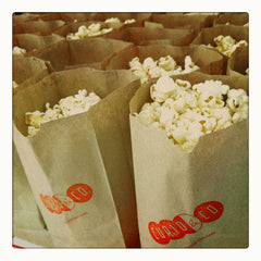 Curio & Co. thinks about popcorn at the movies. Photo of Popcorn in Curio & Co. brown paper bags with logo. Curio and Co. www.curioandco.com
