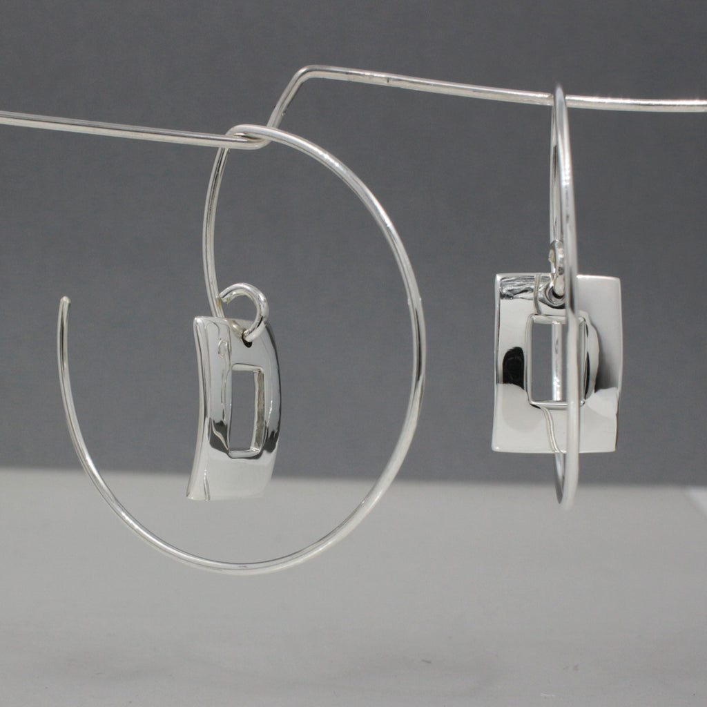 "Hoop's Diameter ~ 35 Millimeters (1.3/8"" Diameter) 20 Gauge Tempered Sterling Silver Wire Inner Small Off-Center Rectangle ~ 14 Millimeters Long X 10 Millimeters Wide (9/16"" Long By 3/8"" Wide) .950 High Polished Sterling Silver Finish How To Wear These Earrings? Just Insert The Earring From The Back Of Your Earlobe And Work Forward Until The Selene Square Earrings Face Forward. These Dimensional Silver Hoop Earrings Look Great From Any Angle."