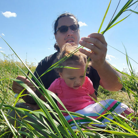 Sean Rayland and his daughter Seantae sitting in the grass picking sweet grass for the people.