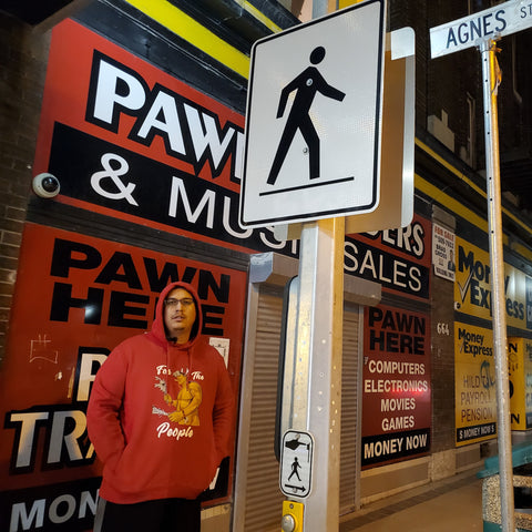 Sean Rayland standing next to a pawn shop in the neighborhood he grew up in. He is wearing the For The People Red Hoodie.