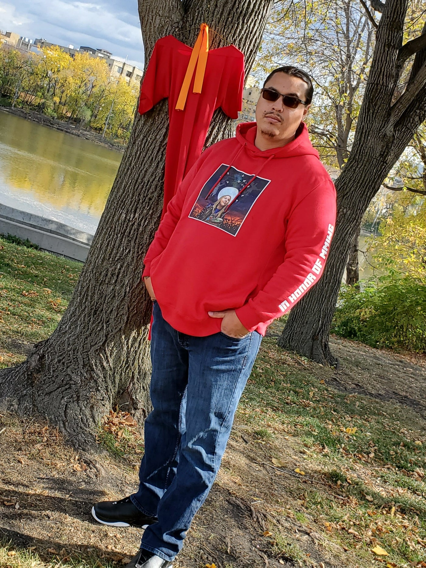 Sean Rayland wearing Not Forgotten Hoodie standing next to the Red Dress symbolizing MMIWG2