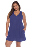 Model posing in the BECCA ETC Breezy Basics Women's Plus Size Plunge Neck Blue Topaz Dress