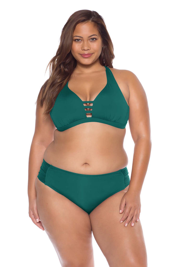 Model posing in the BECCA ETC Color Code Women's Green Plus Size Bralette Bikini Top front