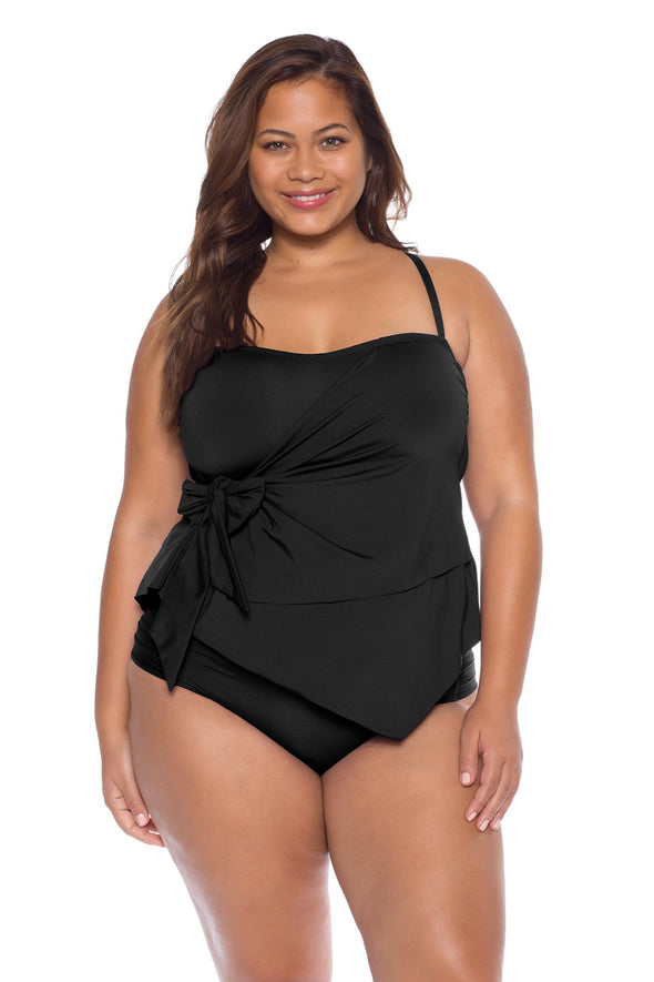 Model posing in the BECCA ETC Color Code women's black plus size tie side tankini top