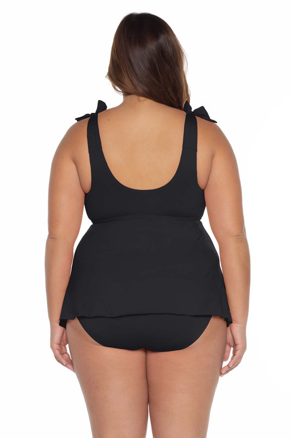 Model's back posing in the BECCA ETC Color Code Women's black plus size tie tankini swimsuit top