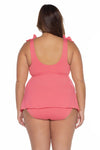Model posing in the BECCA ETC Color Code Women's geranium colored plus-sized tie tankini swimsuit top