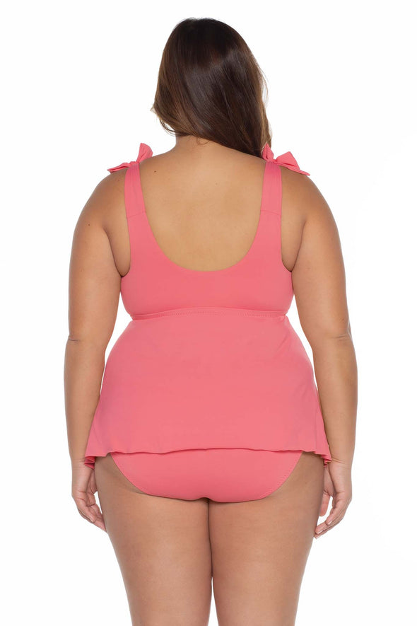 Model's back posing in the BECCA ETC Color Code Women's pink plus tie tankini swimsuit top