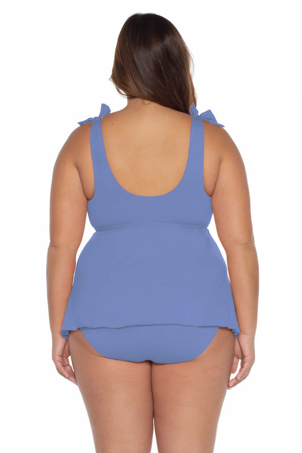 Model's back posing in the BECCA ETC Color Code Women's blue plus size tie tankini swimsuit top