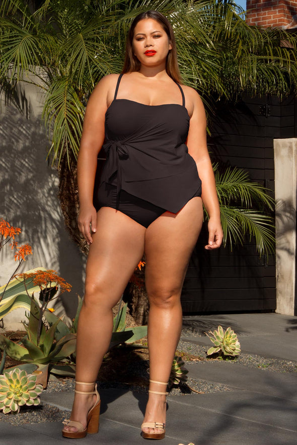 Candid model posing in the BECCA ETC Color Code women's black plus size tie side tankini top