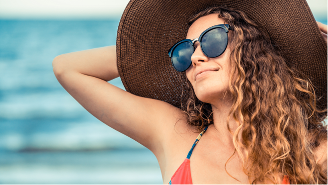 Woman in summer with curly hair exposed to the sun