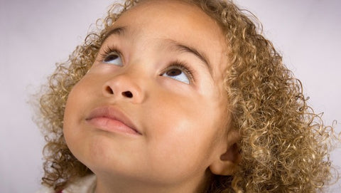 Young mixed girl with curly coily blonde brown hair looking up