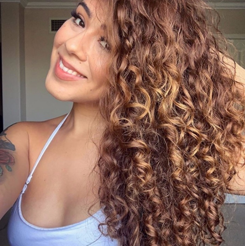 Latina woman with light brown curly hair