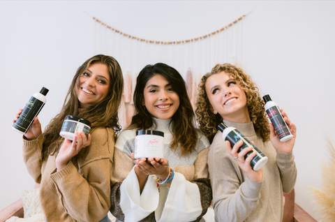 Three young women holding MopTop Hair Products