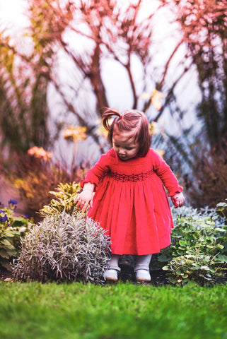 Amelie playing in the garden in her Christmas Coral red velvet smocked dress