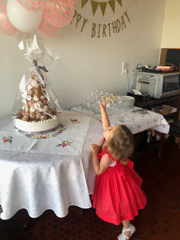 Chiara celebrating her birthday party in our Poppy red Netti smocked dress