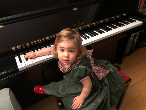 Chiara at the piano in her Fir green smocked dresss with Liberty details! Precious