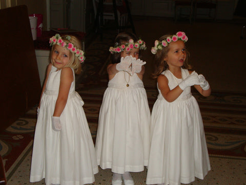 Darling flower girls in handmade white smocked dresses for a chic wedding in France