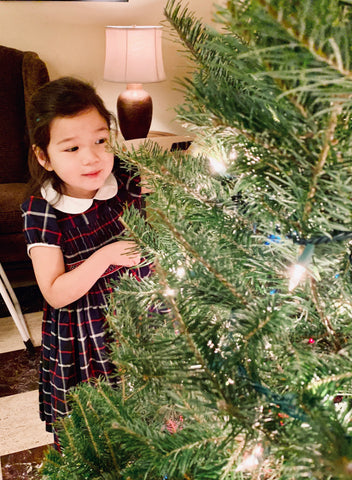 The most adorable little Santa helper decorating the Christmas tree in her special handmade Tartan smocked dress with delicate silver threads.   Thank you to Kate for wearing our dresses with such elegance!