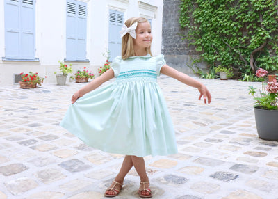 Beautifully hand-smocked celadon green satin cotton Cerise baby and girl formal wear dress for a traditional heritage look. This beautiful and elegant pale green shade is named Celadon.