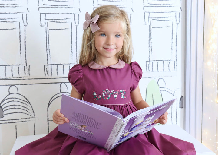 "Handmade plum shade estelle smocked dress with love embroideries. ""The embroideries featuring the word LOVE are inspired by the illuminated manuscripts of the Middle Ages. These precious texts, often poems or sacred writings were embellished by calligraphers. The first letters of chapters were most often decorated with delicate floral patterns. May this dress make your child feel like a Medieval queen!"" - Album Les Triplés"