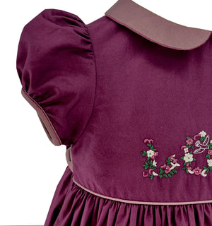 "Handmade plum shade estelle smocked dress with love embroideries. ""The embroideries featuring the word LOVE are inspired by the illuminated manuscripts of the Middle Ages. These precious texts, often poems or sacred writings were embellished by calligraphers. The first letters of chapters were most often decorated with delicate floral patterns. May this dress make your child feel like a Medieval queen!"""