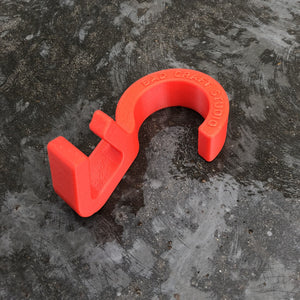 a single bright red hook used to hang bags on a closet rod. The hook sits on a medium grey concrete surface that is a bit splotted. The hook reads BAD CRAFT STUDIO. This photo shows an additional angle looking up at the inside of the hook.