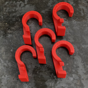 Five bright red hooks used to hang bags on a closet rod. The hooks sits on a medium grey concrete surface that is a bit splotted. Each hook reads BAD CRAFT STUDIO