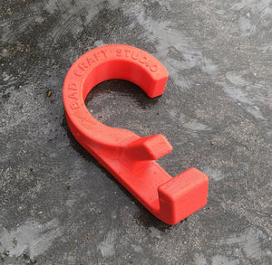 a single bright red hook used to hang bags on a closet rod. The hook sits on a medium grey concrete surface that is a bit splotted. The hook reads BAD CRAFT STUDIO. This photo shows an additional angle looking down towards the face of the hook