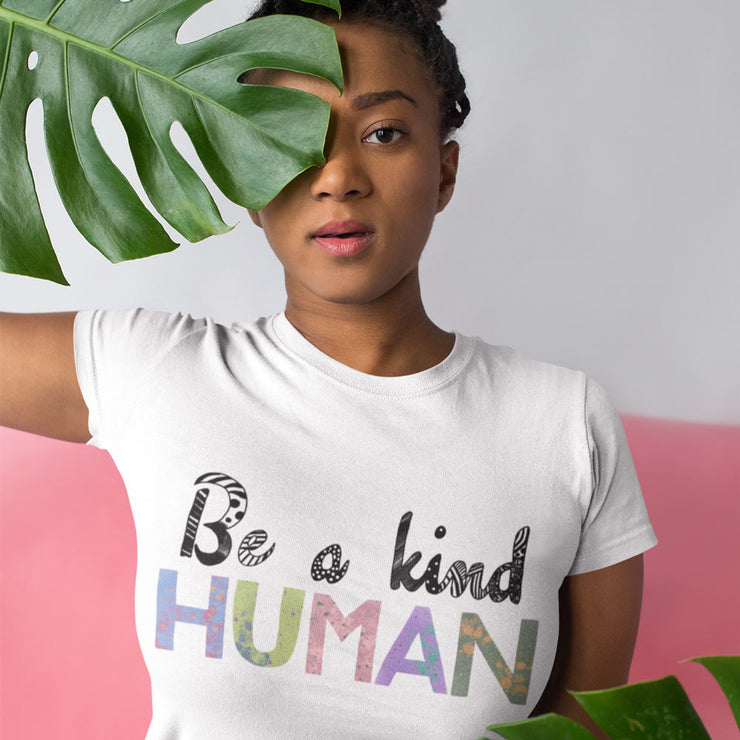 White t-shirt with the words be a kind human printed in a colourful painted font.
