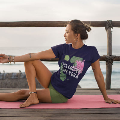 Navy t-shirt with tropical leaves and a flower and the words less coffee more yoga