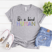 Grey t-shirt with the words be a kind human printed in a colourful painted font.