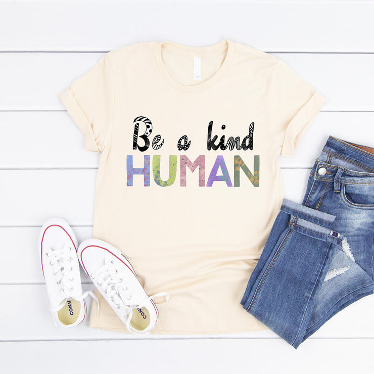 Cream t-shirt with the words be a kind human printed in a colourful painted font.