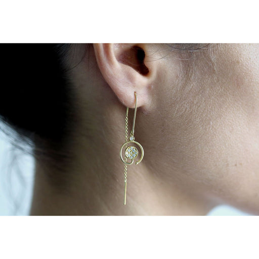 Long gold earrings with white diamonds